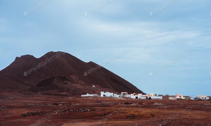 Local village Calhau at the foot of the volcanic crater. Single martian like dry red rock stand out