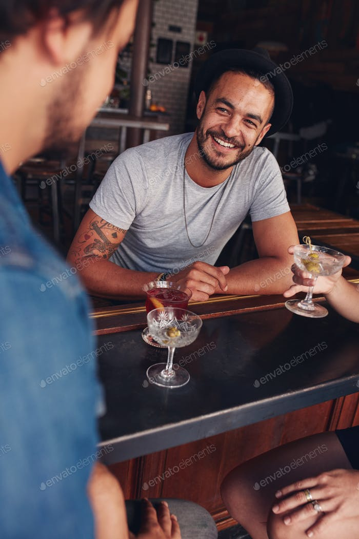 Young friends sitting at a cafe table having drinks