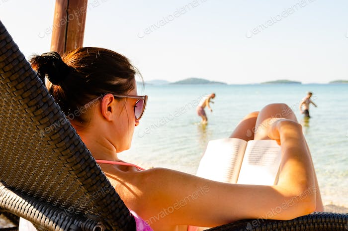 Woman on sun bed on the beach reading a book. People in background walking into sea