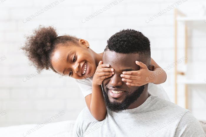 Cute little black girl covering her dad eyes