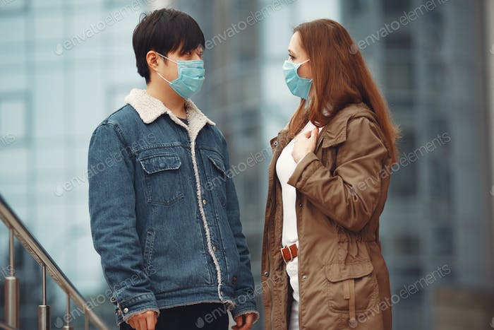 A woman and Chinese man are wearing protective masks