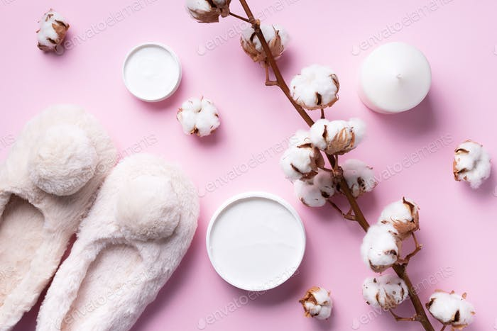 Bathroom accessories, nude fluffy home slippers, cotton flowers, candle, skin care products on pink