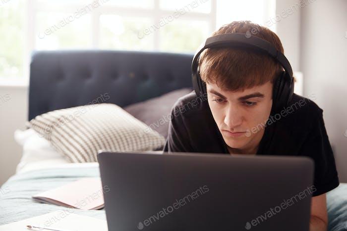 Male College Student trägt Kopfhörer liegt auf Bett im gemeinsamen Haus Arbeiten auf Laptop