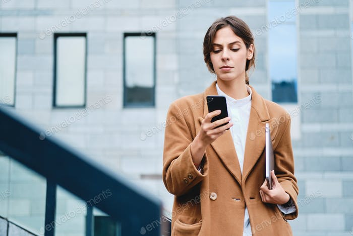 Young serious casual businesswoman in coat with laptop confidently using cellphone outdoor