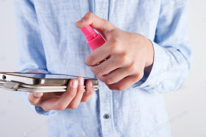 Boy in a pastel blue shirt is cleaning his phone or tablet with antiseptic in a plastic bottle