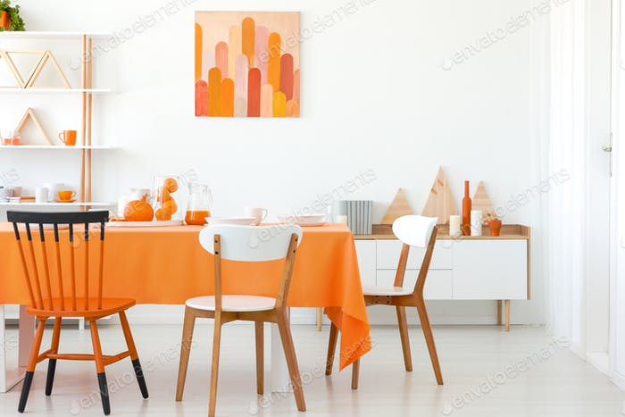 Chairs at table in white and orange dining room interior with po