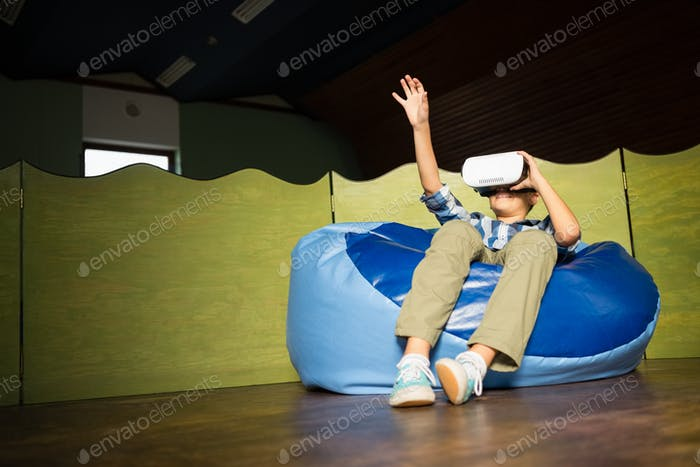 Boy sitting on bean bag and using virtual reality headset