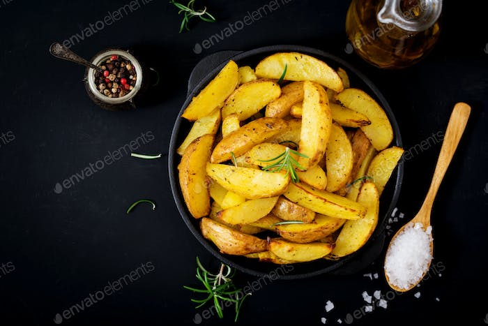 Ruddy Baked potato wedges with rosemary and garlic on a dark background. Flat lay. Top view.