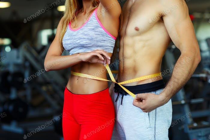 Thumbnail for Happy athletic man and woman with measuring tape in gym
