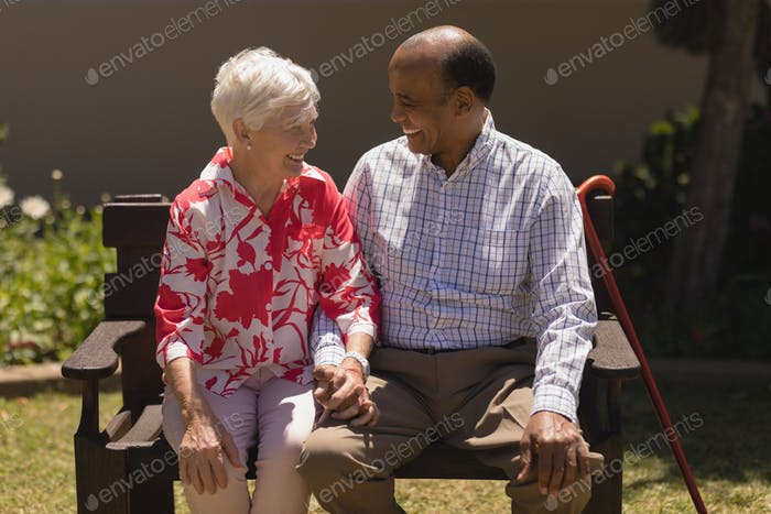 Front view of happy senior couple sitting on bench and looking each other on sunny day in garden