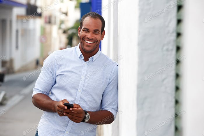 cheerful man standing outside on street with mobile phone