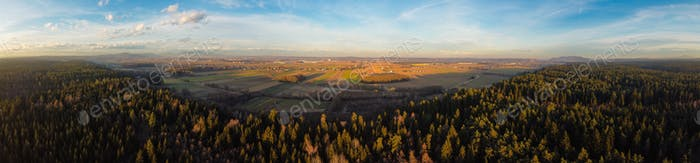 Panorama aerial view from above a forest at rural area with fields and few houses.