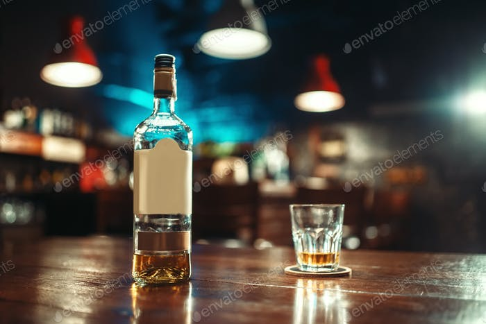 Bottle of alcohol and glass on bar counter closeup