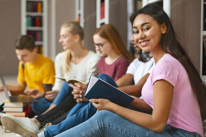 Group of diverse classmates sitting on floor at library