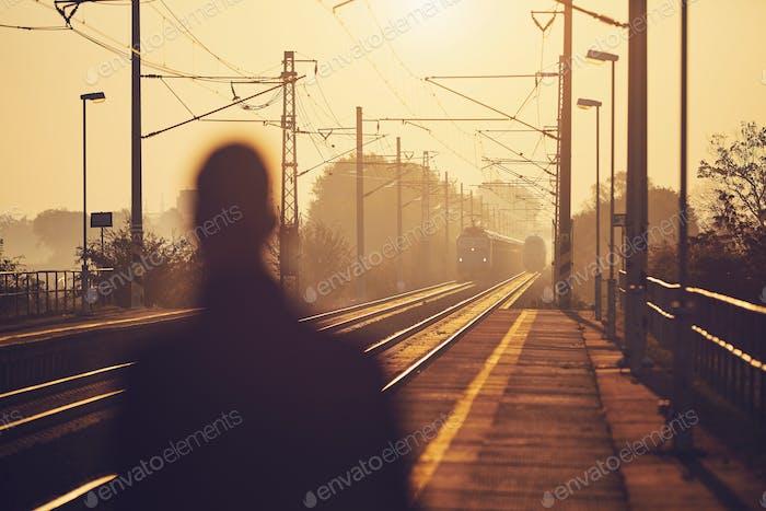 Man waiting at railroad station