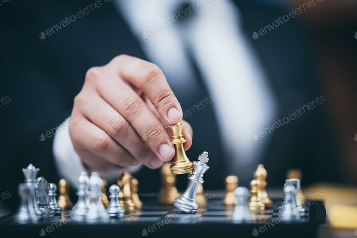 hand of businessman moving chess figure in competition success play