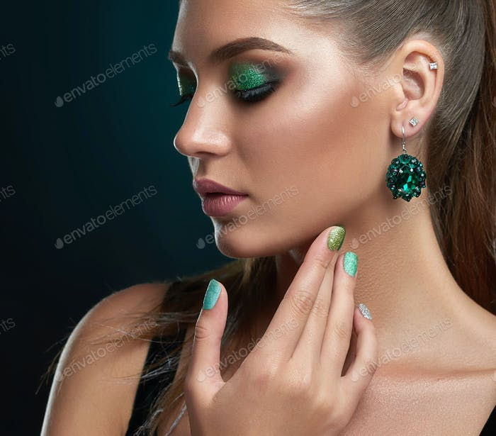 Girl with closed eyes, long eyelashes and makeup in green colors