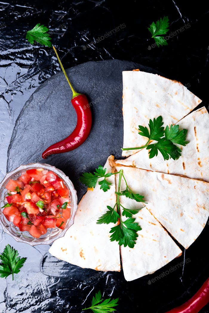 Mexican quesadilla with salsa sauce on black slate stone plate. Chili pepper. Top view.