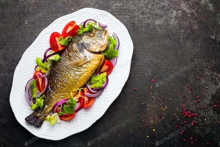 Baked fish dorado. Dorado fish oven baked and fresh vegetable salad on plate. Sea bream