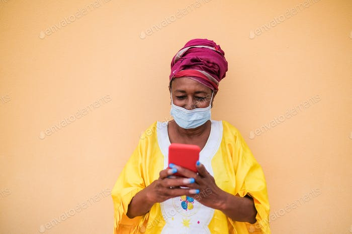 Elderly african woman with smartphone and traditional dress