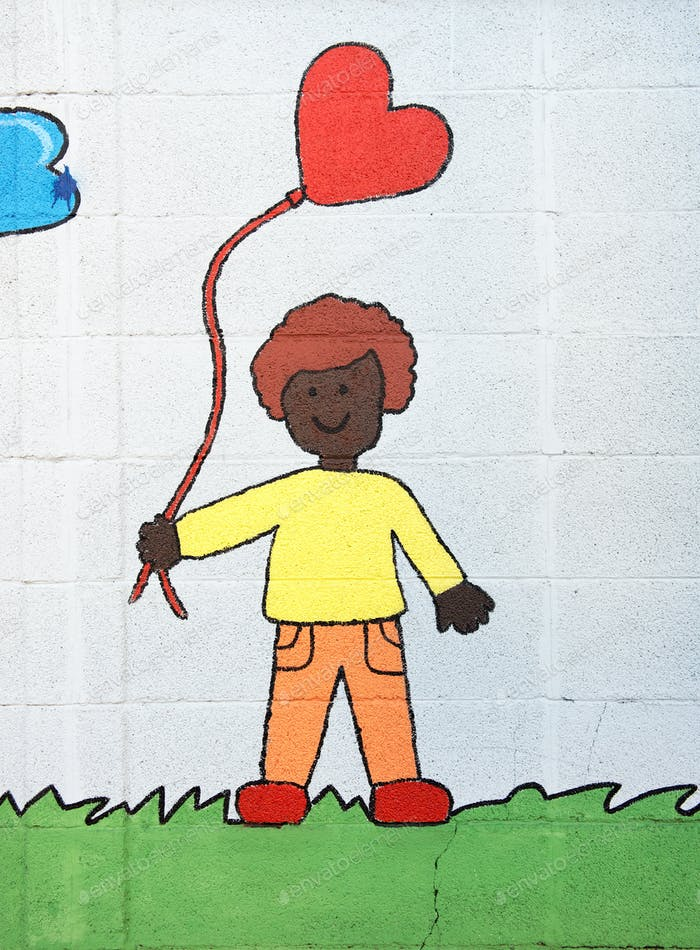 Young boy flying a red heart kite or balloon