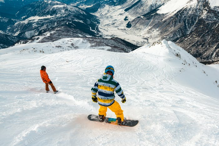 snowboarders is riding down of mountain