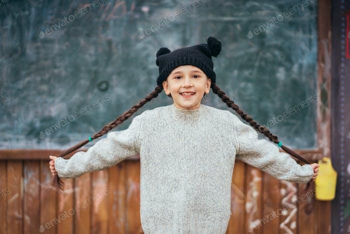 Kleines Mädchen in einem Hut posiert auf dem Hintergrund der Schule Tafel
