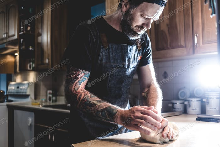 Man kneading dough on kitchen
