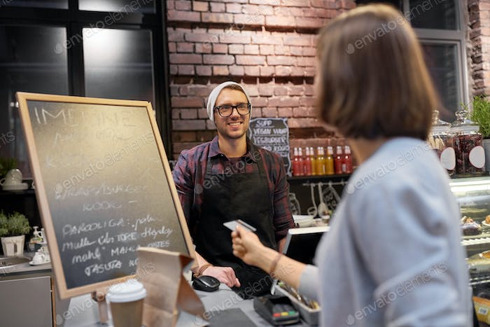 barman and woman paying with credit card at cafe