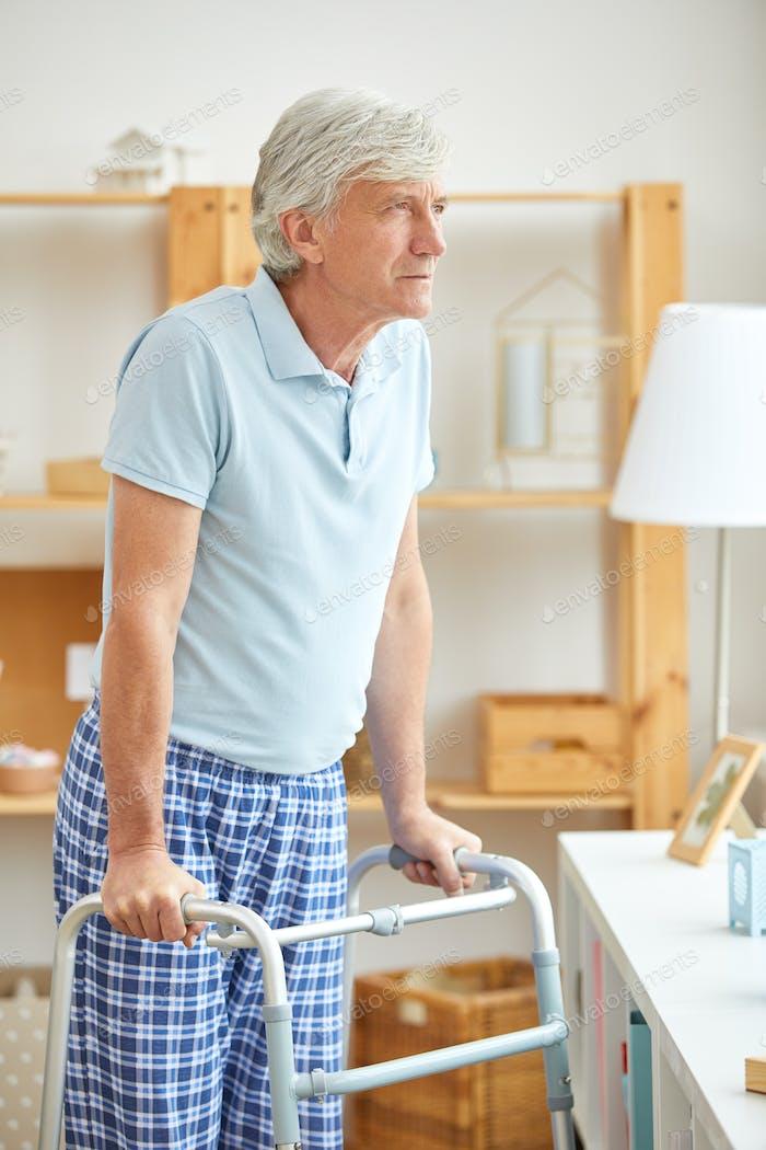 Hombre mayor con walker en casa