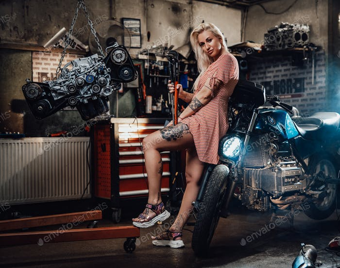 Beautiful blonde girl with tattooed body wearing pink dress posing in garage or workshop