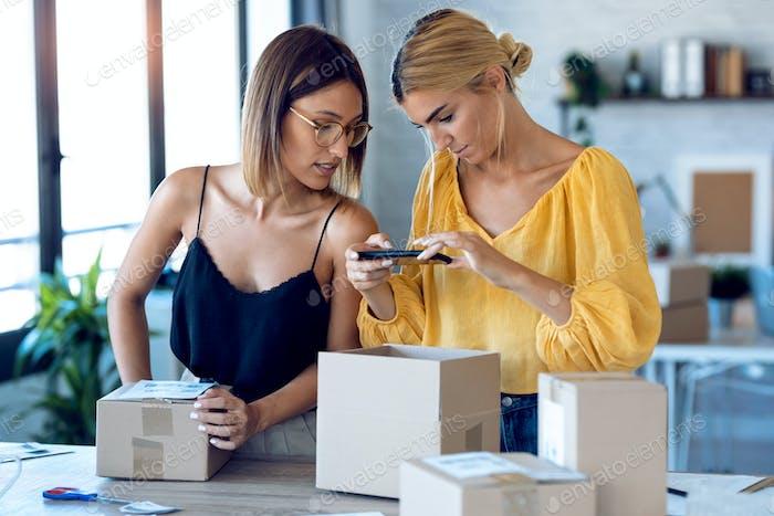 Две красивые внештатные деловые женщины, использующие смартфон, чтобы Фотографии ровать, чтобы продавать онлайн