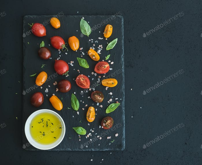 Cherry tomatoes of various color, basil leaves, spices and olive oil