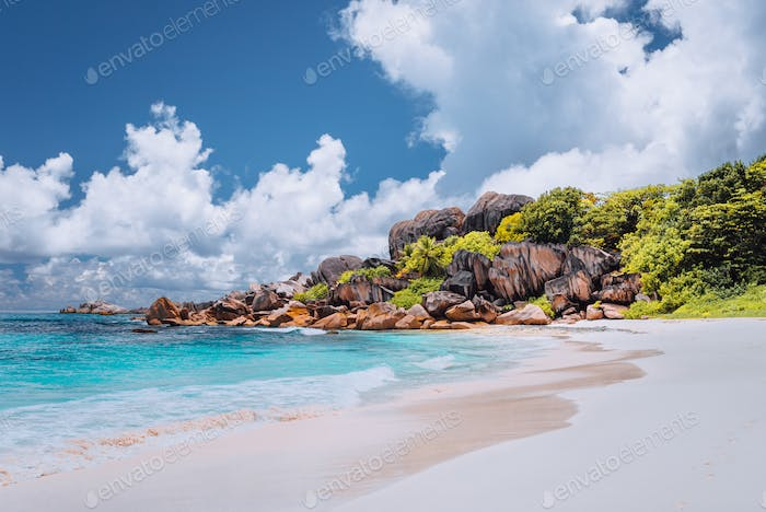 Grand Anse tropical beach in La Digue, Seychelles. Famous granite rock formations and white clouds