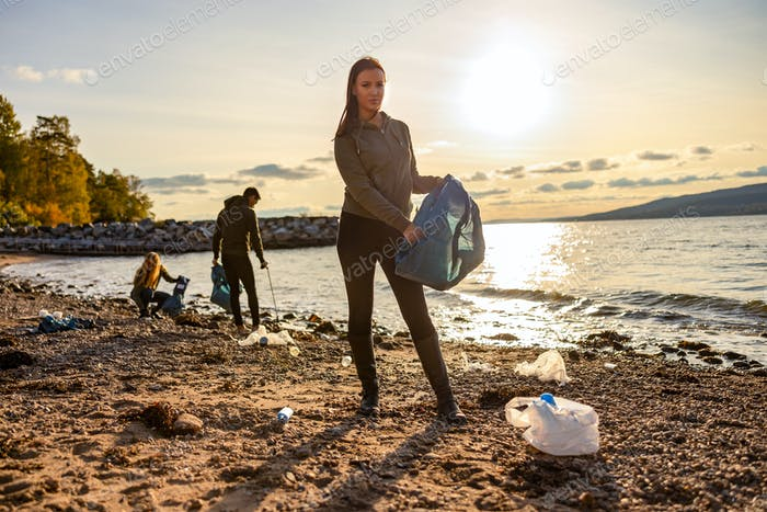 Woman cleaning beach with volunteers during sunset