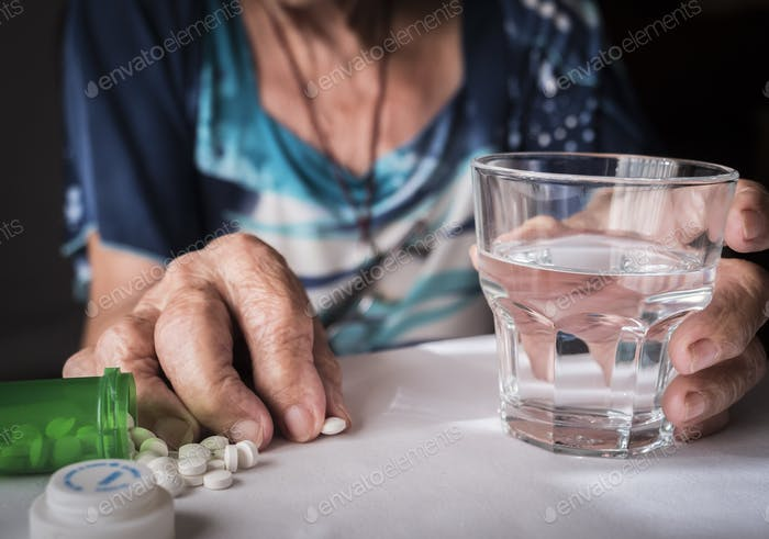 Oldster taking daily medication dose at home