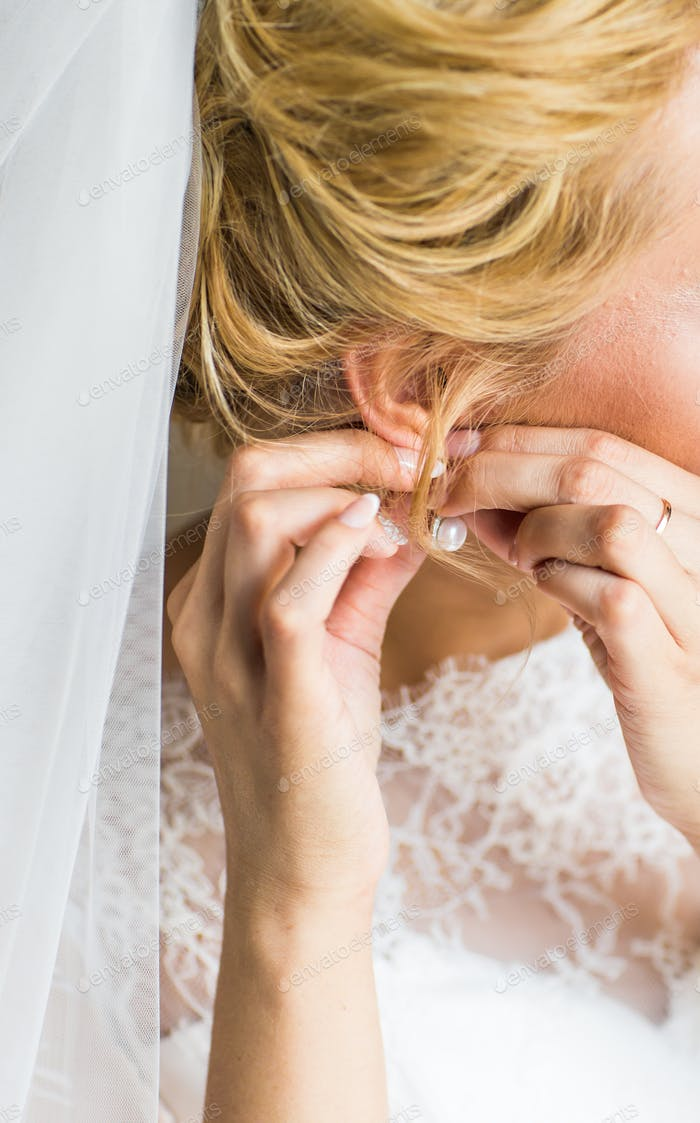 beautiful gorgeous  bride putting on luxury earrings