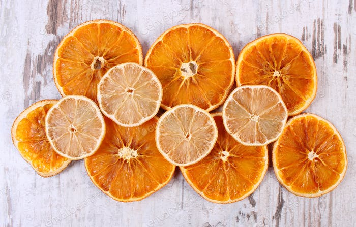 Slices of dried lemon and orange on old wooden background
