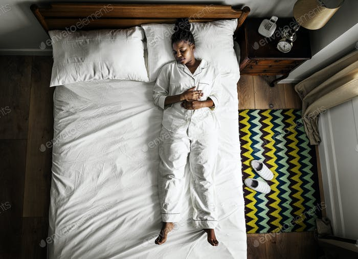 African American woman on bed sleeping alone