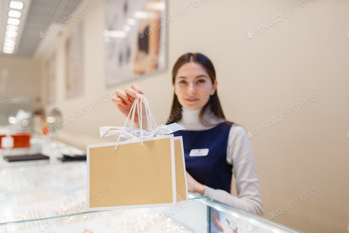 Female seller with shopping bags in jewelry store