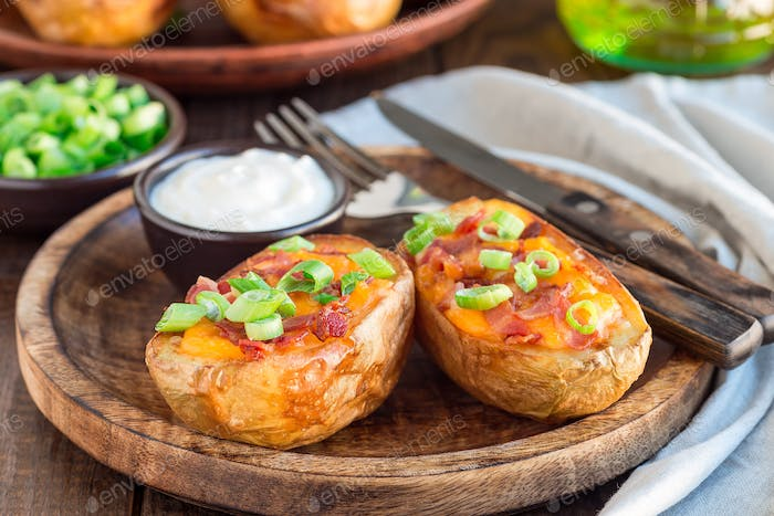 Baked loaded potato skins with cheddar cheese and bacon on woode