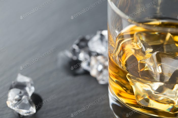 Detail of glass of whiskey and ice cubes shot on the dark background