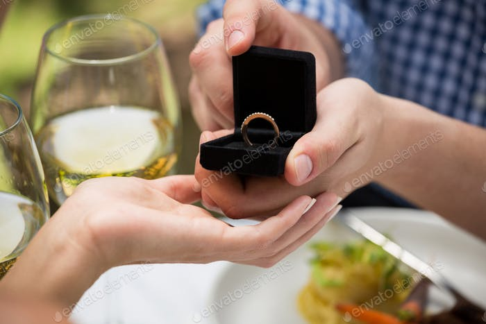 Man giving engagement ring to woman at outdoor restaurant