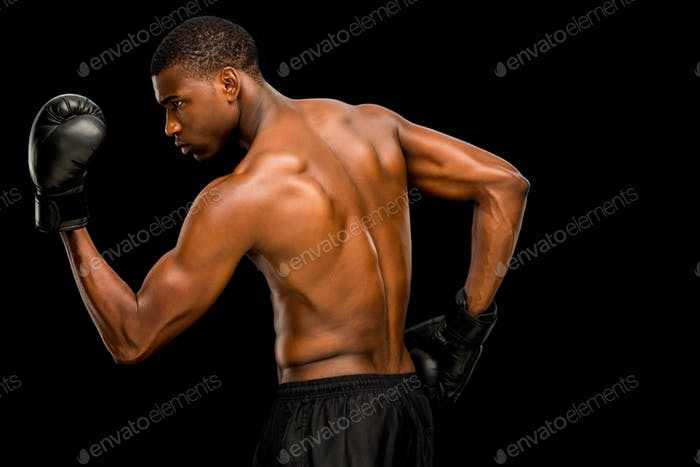 Shirtless muscular boxer posing over black background