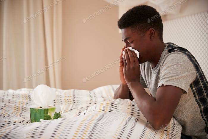 Millennial African American man sitting up in bed blowing nose, side view, close up