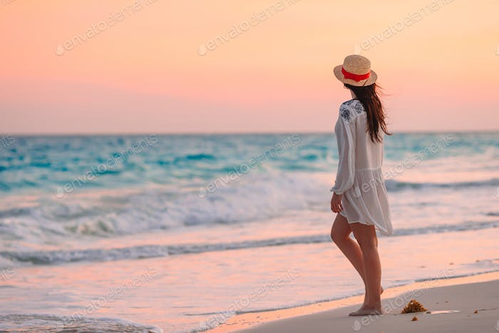 Young beautiful woman on tropical beach in sunset