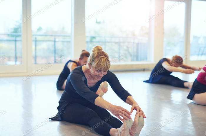 Fit women stretching on floor in ballet class