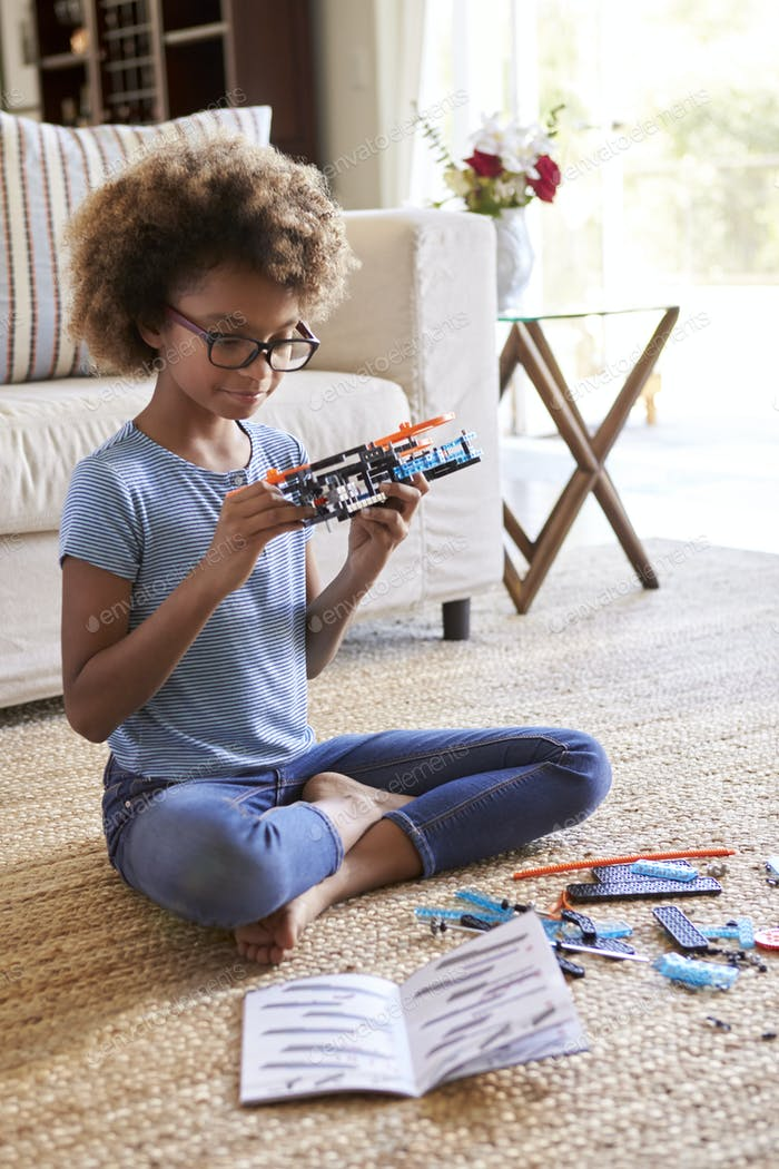 girl sitting on the floor in the living room building a toy from a construction kit, close up