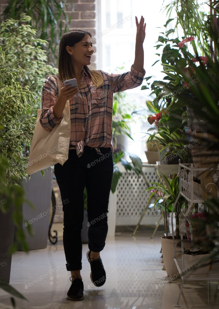 A girl in a plaid shirt with eco bag comes into the store and greets the sellers