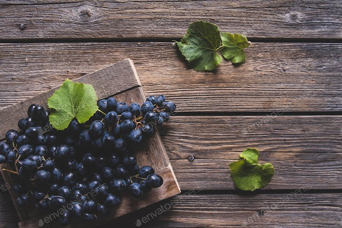 fresh grape with leaves in a wooden box on wooden background